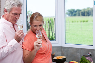 Mature couple smelling at champagne in kitchen