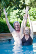 Mature couple with raised arms in swimming pool