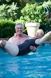 Senior man carrying wife in swimming pool