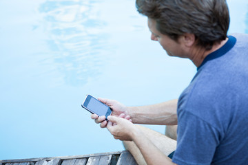 Mature man using smartphone by the poolside