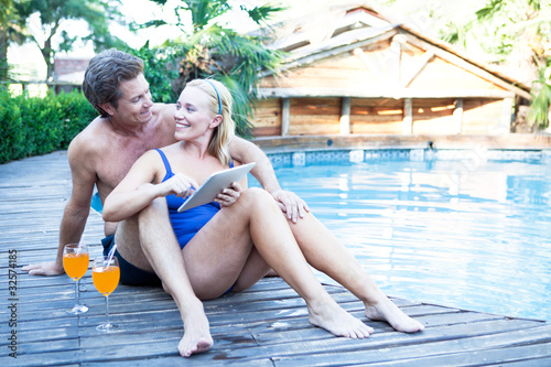 Mature couple with tablet computer and drinks by the poolside
