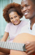 Portrait of a smiling young couple playing a guitar
