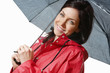 Smiling woman in raincoat holding an umbrella