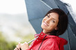 Smiling woman in red raincoat holding an umbrella