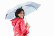 Happy young woman in raincoat holding an umbrella