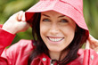 Smiling cute woman in red raincoat outdoors