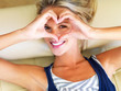 An attractive woman looking through a heart sign