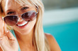 Happy young woman looking through sun glasses