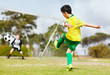 Young boy kicking football towards the goal at goal keeper