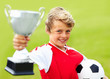 Soccer boy holding trophy and ball against green background