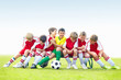 Mischievous soccer kids having fun on bench - copyspace