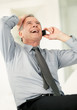 Senior business man laughing while using on cell phone