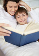 Happy young boy with his mother reading book in bed