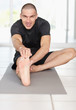 Happy middle aged male stretching his leg while sitting on mat