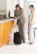 Business couple waiting at the hotel reception with luggage