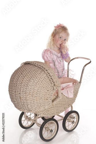 little girl dressed playing with baby carriage