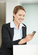 Happy business woman reading message on cell phone