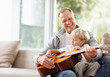 Little boy playing guitar with his father at home