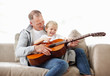 Happy boy playing guitar with his father while sitting in sofa
