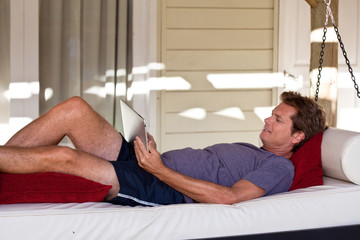 Mature man holding tablet computer in hanging lounger on veranda