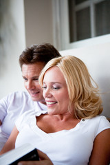 Smiling mature couple looking into book