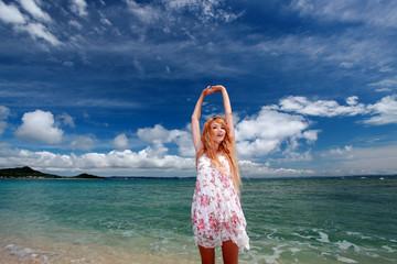 久高島のビーチで空に向かって背伸びをする女性