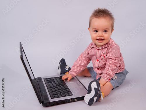 enfant souriant devant l 39 ordinateur portable de magalice. Black Bedroom Furniture Sets. Home Design Ideas