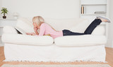 Young blonde woman relaxing with a book while lying on a sofa