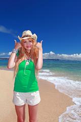 ビーチでガッツポーズする笑顔の女性