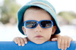 little boy with sunglasses and blue panama on the beach