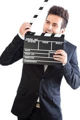 Joven hombre mordiendo claqueta de cine