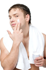 Man putting on cream lotion on face