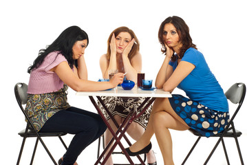 Unhappy women sitting at table