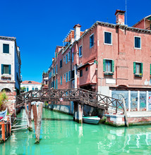 Colored Venice canal with bridge and houses in water, Italy