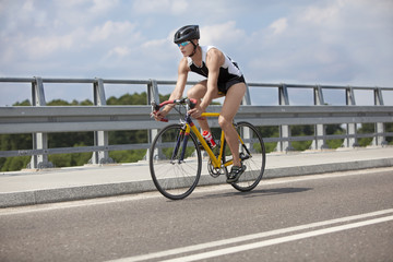 Triathlete biker pedaling on race bicycle