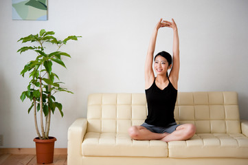 beautiful asian woman stretching on the couch