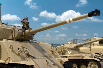 Cute boy saluting on the israeli tank. Museum of tanks. Israel.