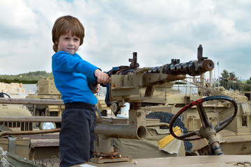 A little boy stands in a jeep with a machine gun and aims.