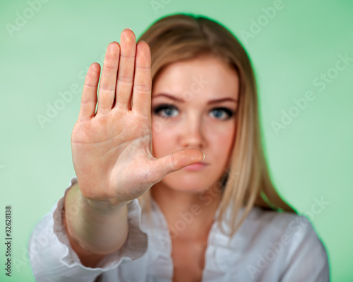 Young  women holding hand in front of camera showing a sign STOP