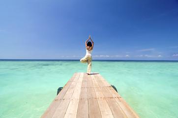 asian yogo on beautiful beach