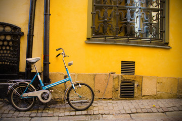 Blue small bicycle stands against a yellow wall in the old town