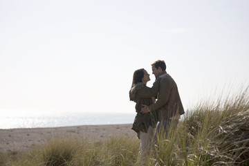 A pregnant woman and her partner standing amongst the sand dunes