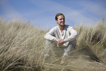 A young man sitting amongst the sand dunes, smiling