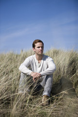 A young man sitting amongst the sand dunes, looking thoughtful