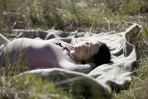A pregnant woman sleeping amongst the sand dunes