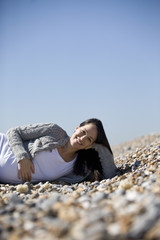 A pregnant woman lying on the beach, smiling