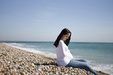 A pregnant woman sitting on the beach