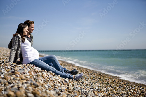 A pregnant woman and her partner sitting on the beach