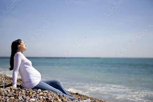 A pregnant woman sitting on the beach, relaxing