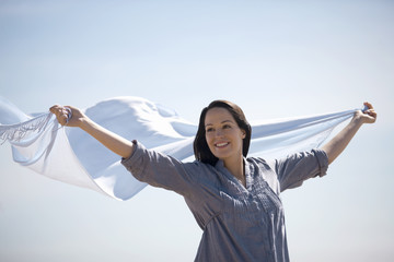 A pregnant woman holding a scarf into the wind